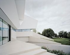 Futuristic Villa Design in Sculptural Architecture and Simple Interior : Contemporary Driveway Design Made From Concrete Staircase Ideas Among White Color Decor Used Green Landscaping Edging As Home Inspiration