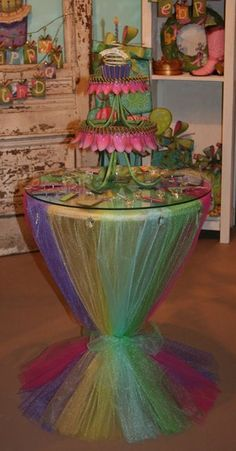 Table Display: Yards & yards of different colored tulle completely cover a round table & gather with a bow to flare at the base. The round glass top holds it all in place.  I want to do this with just normal fabric