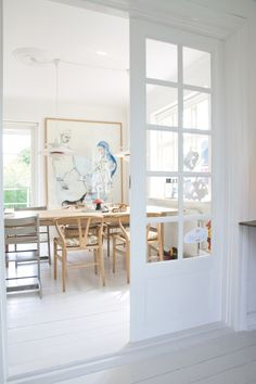 White and blonde wood dining room in Denmark.Via planete deco.