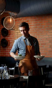 Houston restaurants serve up waitstaff style and fashion Peter McAleer wears a chambray shirt, striped tie, blue suede shoes and a leather apron made by Stash Co. of Sealy, at Sparrow Bar & Cookshop. Photo: Michael Paulsen, Staff / © 2013 Houston Chronicle