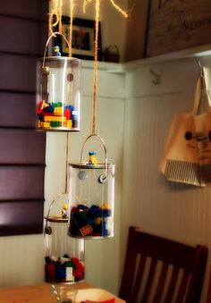 Clear buckets with legos hung from light fixture over table  - for Zach's lego party.