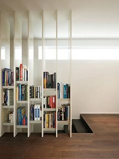 A unique room divider that adds architectural interest and serves as a bookcase. The open shelves don't block the light from the window. They also visually expand the space into the stairwell, making it feel larger.