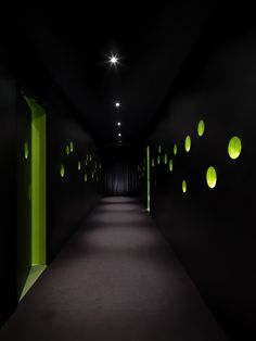 Circular holes in the corridor walls allow glimpses into the bright green meeting rooms.|Leo Burnett Singapore