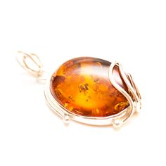 This classic pendant features a simple, rounded off Amber stone with elegant silver additions.