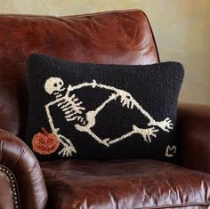 """Bones Mcbones Pillow  Let Bones McBones add a little holiday """"spirit"""" to your home. He's pictured with a pumpkin on a pillow made of hand-hooked wool with a cotton velveteen back. $39.99"""