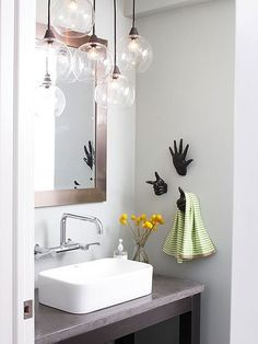 Bathroom Lighting Ideas Work of Art The organic shape of this blown-glass light fixture works well in the contemporary-style bathroom. Modern spaces can feel cold and be full of hard edges, but the round globes on the light fixture and the hand-shape towe Small Bathroom Vanities, Bathroom Design Small, Vanity Bathroom, Budget Bathroom, Bathroom Ideas, Bathroom Remodeling, Bathroom Designs, Remodel Bathroom, Vanity Sink