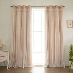 Best of both worlds: These look super-sheer (and the tulle overlay is), but they're blackout curtains. (Decorinnovation Sheer Overlay Grommet Top Blackout Window Curtain Panel Pair in Pink via Bed, Bath & Beyond)