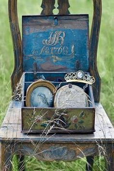 interesting mix, old chair, old tin plus treasures