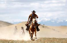 Wrangler Shad Boardman rides into a pasture during Montana Horses' final horse drive outside Three Forks, Montana, on May 6, 2012.