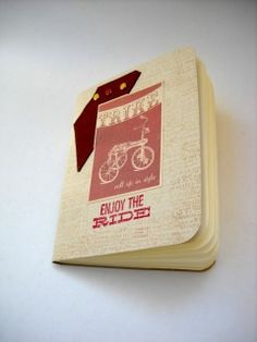 """Compact softcover sketchbook lightly Altered with hand stamped, typewriter text background. I added brown leather with three brads of yellow and red. An image of a tricycle with tattoo lettering and hand stamped phrase, """"Enjoy the ride"""".  Inside are 64 pages of Ivory, Fabriano sketching paper. The flat edged spine has  a brown chain stitch running down the spine. Great for quick sketches on the go.  FEATURES - 5½"""" x 4¾ - Flat spine - Chain stitch using brown waxed linen thread - 64 pages of…"""