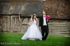 Bride and groom walking outside the barns at Avoncroft Museum of Historic Buildings (avoncroft.org.uk). Rob & Sarah Gillespie Photography