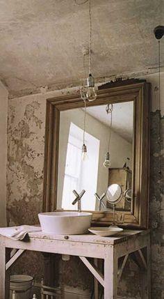 rustic bathroom, Edison bulb light, reclaimed wood table as base, basin sink framed mirror, plaster walls