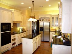 A charming yellow kitchen benefits from granite countertops and under-cabinet lighting.