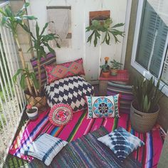 Bohemian decor on the balcony. Just so fun with all those colors and patterns on the rugs and pillows.