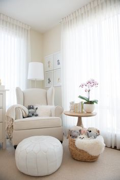 Beautiful gender neutral nursery features a nursing corner boasting a collection of frames Sharon Montrose The Animal Print Shop Prints over a PB Kids Wingback Nailhead Rocker situated next to a round salvaged wood accent table and white Moroccan leather pouf illuminated by a polished nickel floor lamp surrounded by windows dressed in white sheer curtains.