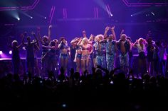 Britney dancing on stage with fans at the Femme Fatale Tour.