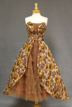 Vintage 1950's Cocktail Dress in Floral dark beige voile w/ sepia & maize colored flowers accented w/ clear sequins. Fitted, strapless bodice inset w/ pleated solid mocha tulle. Full tulip skirt in floral voile over ruffled tulle underskirt. Boned bodice, detached crinoline slip, rear metal zipper. VINTAGEOUS.COM