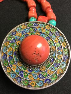 A large amulet pendant box, enamelled silver and a round cabochon coral. Mongolia, worn by women of Uzemchin tribe. Circa 1900