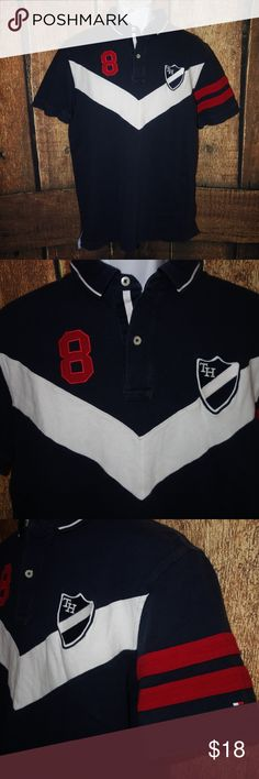 """Tommy Hilfiger Polo Shirt Men L Vintage Shield #8 Tommy Hilfiger Polo Shirt Men L Vintage Shield #8 Blue White Short Sleeve b16 Preowned in good condition Mild was wear Classic Polo Fold down collar button neck TH shield on the chest #8 embroidered on the other side Length from shoulder to hem is 29"""" Chest from under arm to under arm is 22"""" I have other items like this listed Thank you for looking! Tommy Hilfiger Shirts Polos"""