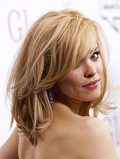 Rachel McAdams medium hairstyle. All-over layers create volume and glamour, while side bangs keep the look soft around the face.