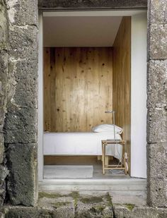 interior.architects. simple bedroom, stone building, wooden inteior, white linen, E/C House by SAMI-arquitectos