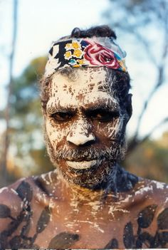 In this picture Balang Djimarr (a speaker of Kuninjku) has painted his body and face. His body has a plant design painted in black ochre. This plant is called wurrurrumi in Kuninjku which is a vine that botanists call Tinospora smilacina. This is also the name of a song series that Djimarr sings. That's why he has that design painted on his body. On his face he has white ochre or delek splattered in a design known as bedjek-bedjek.