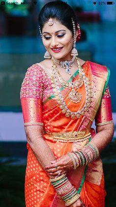 South Indian bride. Gold Indian bridal jewelry.Temple jewelry. Jhumkis. Pink and orange silk kanchipuram sari.Braid with fresh jasmine flowers. Tamil bride. Telugu bride. Kannada bride. Hindu bride. Malayalee bride.Kerala bride.South Indian wedding.