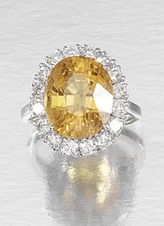 YELLOW SAPPHIRE AND DIAMOND RING.  Centring on an oval yellow sapphire within a boarder of claw-set brilliant-cut diamonds