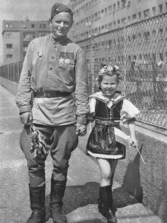 World War II, in Russia – the Great Patriotic War (22 June 1941 – 9 May 1945). Russian soldier with a Czech girl in her national costume. Prague, May 1945.