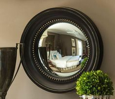 large, round convex mirror with a black frame - centerpiece of collage above couch