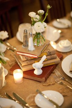 Interesting cover idea Book Centerpieces- wrap them in paper and label them with favorite or themed titles
