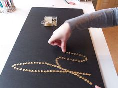 create words with brass push pins in a foam board and frame