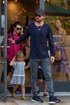 Scott Disick wearing Saint Laurent Small Square Vintage Sunglasses, Lids Flatbill Trucker Hat, Adidas Ultra Boost in Black, Saint Laurent Original Low Waisted Skinny Jean in Washed Grey Stretch Denim and John Elliott L/S Classic Mercer in Dark Navy