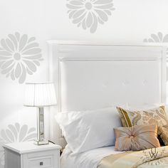 Large gray vinyl flower wall pattern on a white wall behind a  white bed and nightstand. The flowers are equally spaced and each vinyl flower features a number of petals of different sizes.
