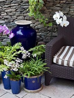 Create a vignette in your seating area. In this design by Robert Hursthouse, a gorgeous urn and orchids add to the elegant tapestry of color and texture. Consider moving an indoor vase or urn into an outdoor space for the summer months.