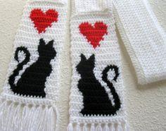 Chat blanc foulard. Tricot écharpe au crochet chat noir des silhouettes et des coeurs rouges. Écharpe longue, maigre avec des chats