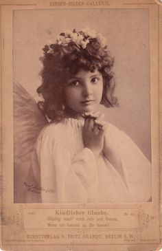 This unusual cabinet card is an image of a beautiful young girl with angel wings. Her hands are clasped in prayer and she has a hopeful expression.