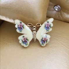 Beautiful Floral Enamel Butterfly! Lovely ornate floral butterfly enamel front and beautiful derailed gold tone back with roll over lock clasp. No markings that I can see. Vintage Jewelry Brooches