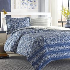 A batik style medallion is paired with a strong geometric stripe border in this dynamic blue and white ensemble. The engineered stripe border acts as an accent at the base of the bed and enhances the hand crafted look of the design.