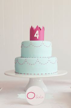 A light blue two-tier birthday cake with pink detailing — topped off by a pink paper crown  — was the crowning jewel of the dessert table. Source: Branco Prata
