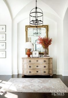 In the foyer, a Dessin Fournir lantern is suspended above a pale chest of drawers and gold mirror, both by Formations at Jerry Pair.