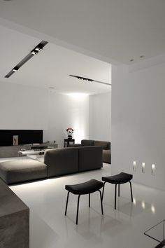 All-white interior with dark furniture and Kreon lighting. Designer unknown.