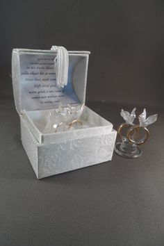Dit bedankje is een chique bruidig doosje met erin glazen ringen met duiven erop. Het is hand bewerkt met 22 kt goud  De tekst in het doosje kunnen we vervangen voor jou tekst