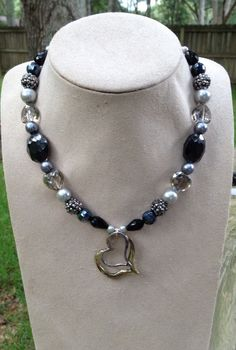 Nk-5 Midnight Rendevous Perfect for your lover, this whimsical piece features midnight blue glass stones, funky hematite spiked beads and heart shaped smoky beads.  Length 18-20 inches.  $40