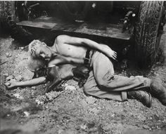 Marine and his dog sleep on rocks, Okinawa, 1945