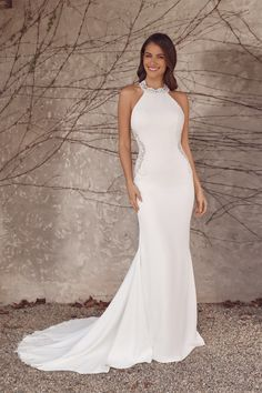 Turn heads in this crepe fit and flare gown featuring a jewel neckline with a lace collar. Beaded lace side cutouts lined in shapewear mesh are paired with a low, open back to make you feel confident and sexy on your wedding day.