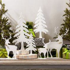 Create a winter wonderland with a touch of sparkle! Featuring a 6-piece woodland tabletop decoration set crafted in iron and accented with white glitter.
