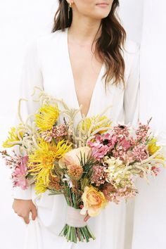 """From the editorial """"Modern-Boho Wedding Inspiration That Was Tailor Made for the Free Spirited Bride."""" Of the Flowers created the most incredible boho arrangements that provided a pop of color to the neutral surroundings. More on SMP!  Photographer: @elliekoleen Floral Design: @oftheflowers  #weddingbouquet #bohobouquet #bohoflowers #bohowedding"""