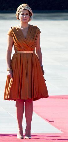 Reina Máxima de Holanda   Acto: Visita oficial a Japón.   Fecha: 29 de octubre de 2014.   'Look': La Reina apostó por un vestido en tono naranja de escote en 'V' y tableado firmado por el diseñdor Mattijs van Bergen. Combinó su diseño con un tocado, al tono, de Fabienne Delvigne y 'stilettos' metalizados, de Natan