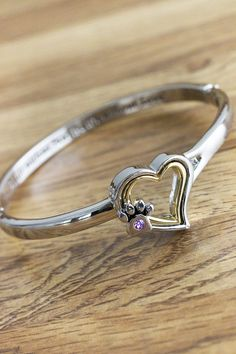 A sentimental affirmation of love for animals -- A life without paws is a life without love -- rests against your wrist on our sweet crystal paw print and heart bangle bracelet.